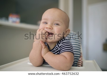 Happy little baby boy of one year old smiling while sitting in high chair at home