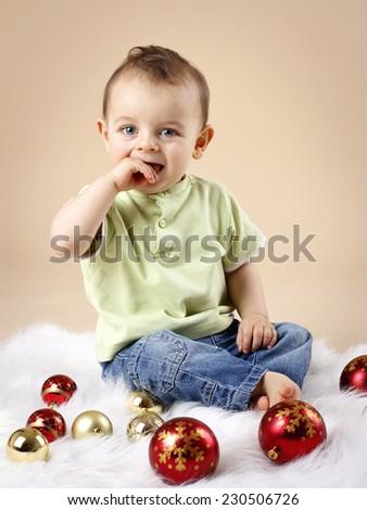 Happy little baby boy with christmas balls - stock photo