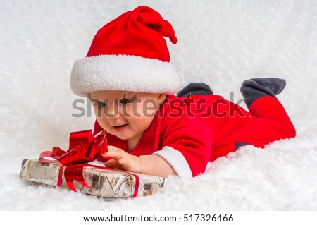 Happy little baby celebrates Christmas with Christmas costume and gift