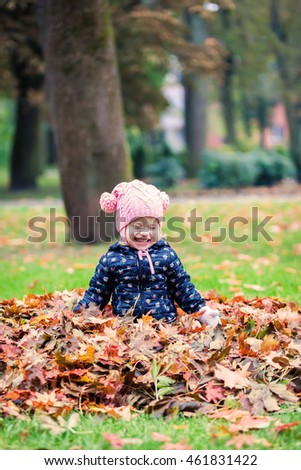 happy little baby girl laughing and playing with leaves in the autumn park