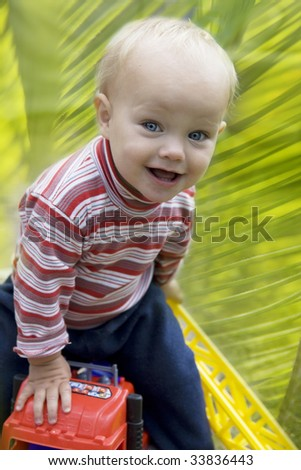 Happy little blond boy driving a toy car outdoor in the park