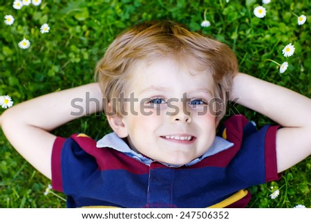Happy little blond boy with blue eyes laying on the grass in the park. On warm summer day. Kid dreaming and smiling. - stock photo