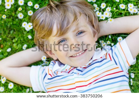 Happy little blond child with blue eyes laying on the grass with daisies flowers in the park. On warm summer day. Kid boy dreaming and smiling. - stock photo