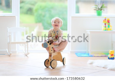 Happy little blonde toddler girl riding on wooden horse indoors in a beautiful room with big window and tiles floor - stock photo