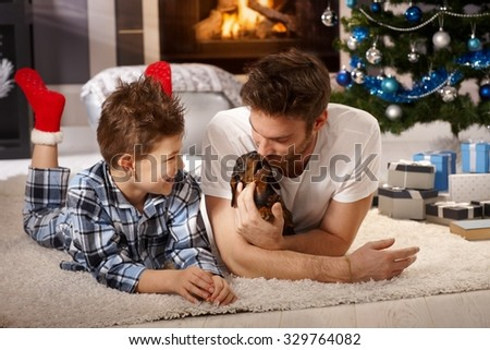 Happy little boy and father playing on floor with dachshund puppy at christmas time. - stock photo