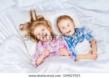 Happy little boy and girl in bed