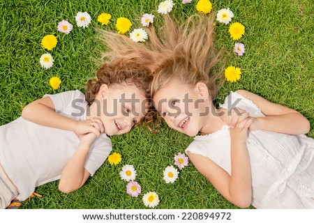 Happy little boy and girl lying on the grass at the day time. Concept of a brother and sister forever. Heart laid out on the grass of the colors, the concept of Valentine's Day - stock photo
