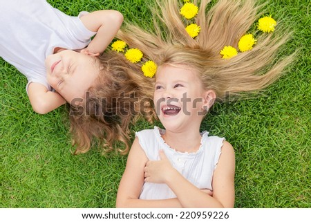 Happy little boy and girl lying on the grass at the day time. Concept of a brother and sister forever. - stock photo
