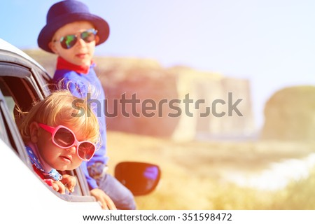 happy little boy and girl travel by car in mountains, kids travel - stock photo