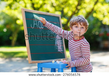 Happy little boy at blackboard practicing writing letters, outdoor school or nursery - stock photo