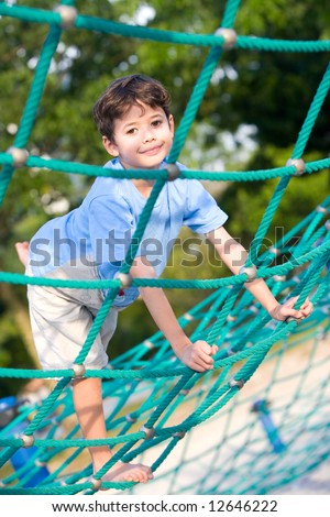 Happy little boy balancing on rope activity in outdoor playground - stock photo