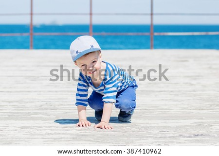 happy little boy crawling outdoors on sea background