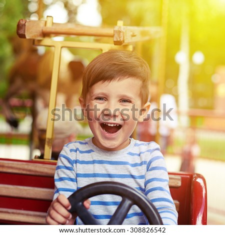 happy little boy driving a car on merry-go-round - stock photo