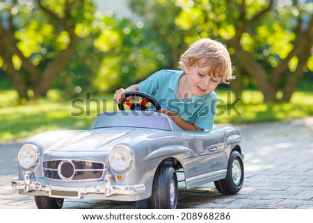 Happy little boy driving big toy car and having fun, outdoors. - stock photo