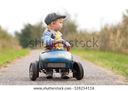 Happy little boy driving big vintage old toy car and having fun, outdoors. Kid leisure on autumn day - stock photo