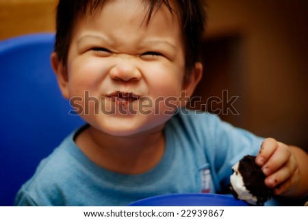 Happy little boy eating an ice cream sandwich - stock photo
