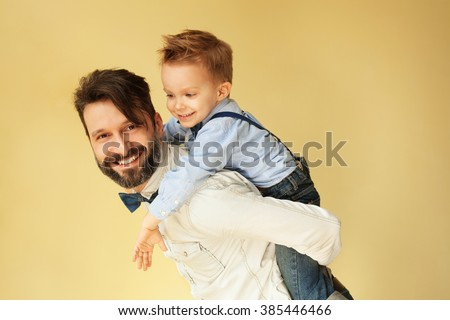 Happy little boy enjoying with riding on father'??s back - stock photo