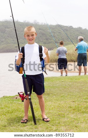 happy little boy fishing with grandpa and brother - stock photo