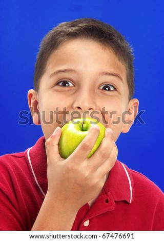 Happy little boy holding and eating fresh apples on blue background. - stock photo