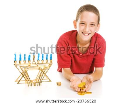 Happy little boy holding Hanukkah gelt he won playing dreidel.  Isolated on white. - stock photo