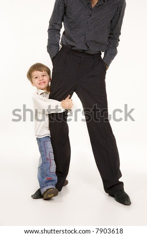 Happy little boy holding his father's leg