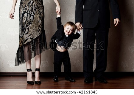 happy little boy holding his parents by the hand - stock photo