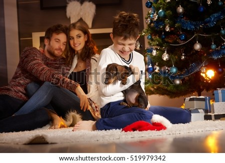 Happy little boy holding puppy receiving for christmas, parents watching from background.