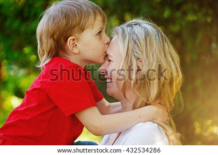 Happy little boy hugging and kissing his mother over green background. Children and happy family concept - stock photo