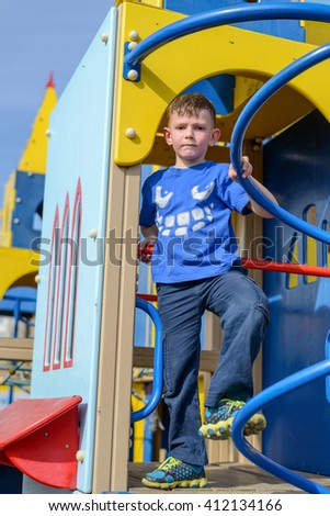 Happy little boy in blue shirt and pants having fun on play castle with blue sky behind him - stock photo