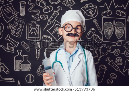Happy little boy in doctor costume holding syringe on dark background with pattern. The child has mustache and glasses