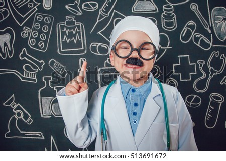 Happy little boy in doctor costume lifts thumbs up on dark background with pattern. The child has mustache and glasses.