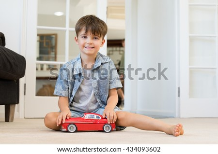 Happy little boy in living room with red toy car. Smiling child playing with car sitting on the floor. Smiling kid looking at camera and playing at home.