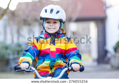 Happy little boy in safety helmet and colorful raincoat riding his first bike and having fun on cold  day, outdoors. Active leisure with children in winter, sping or autumn. - stock photo