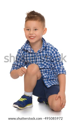 Happy little boy in shirt and shorts kneeling on the floor. He expresses his emotions - Isolated on white background