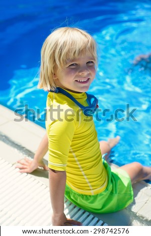 Happy little boy in swimming goggles in the swimming pool - stock photo