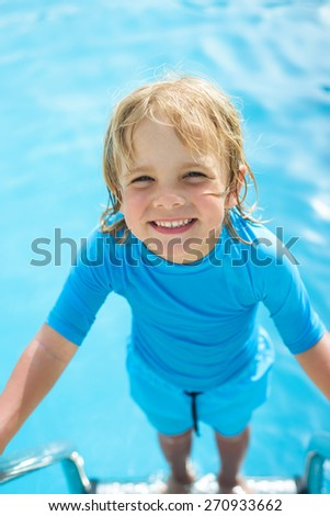 Happy little boy  in the swimming pool - stock photo