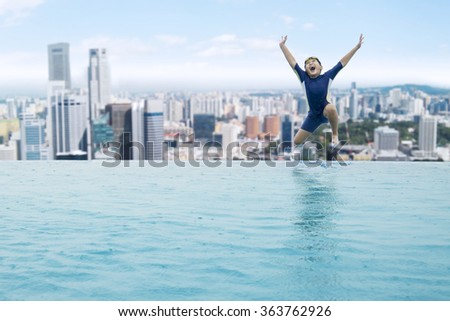 Happy little boy jumping into an infinity swimming pool at sunny day - stock photo