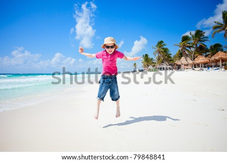 Happy little boy jumping on tropical beach - stock photo