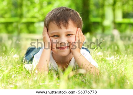 happy little boy laying on the grass in the park - stock photo