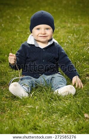 Happy little boy on park meadow - stock photo