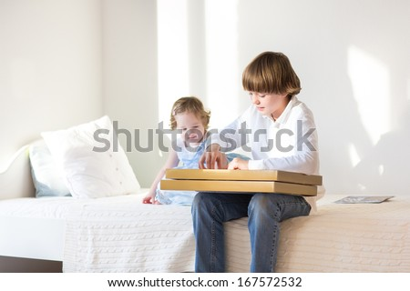Happy little boy opening his present sitting on a white bed next to his baby sister on a sunny morning - stock photo