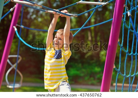 Happy little boy playing at playground in summer day