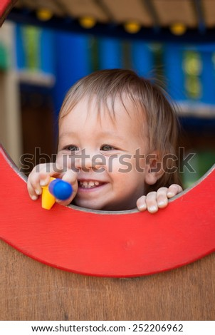 Happy little boy playing at the playground in the park - stock photo
