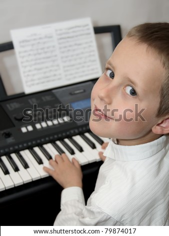 Happy little boy playing electric piano, keyboard. Educational illustration of music lessons. - stock photo