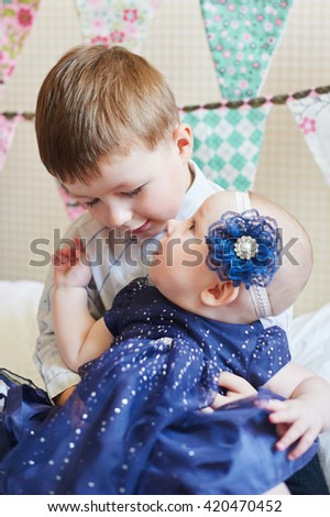 Happy little boy playing with a baby, his sister indoors - stock photo