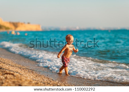 Happy little boy playing with ball on tropical beach - stock photo