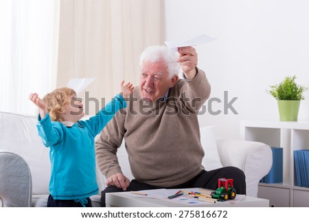 Happy little boy playing with paper airplane - stock photo