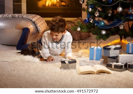 Happy little boy playing with puppy at christmas tree.
