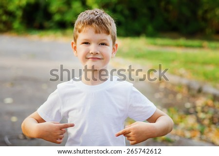 Happy little boy  pointing his fingers on a blank t-shirt, a place for your advertising. Childhood concept. - stock photo