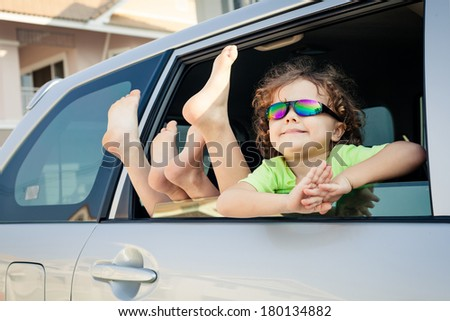 happy little  boy sitting in the car - stock photo